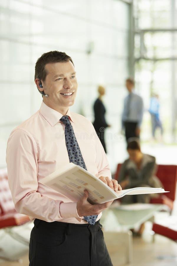 Homem de negócios Using Bluetooth While que guardara o dobrador no escritório foto de stock