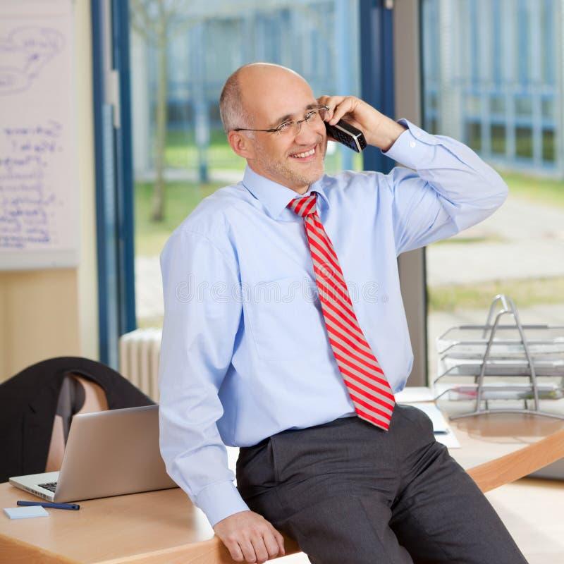 Homem de negócios Using Cordless Phone ao sentar-se na mesa imagem de stock