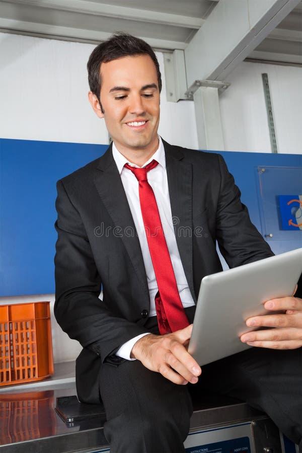 Homem de negócios Using Digital Tablet na lavanderia foto de stock royalty free