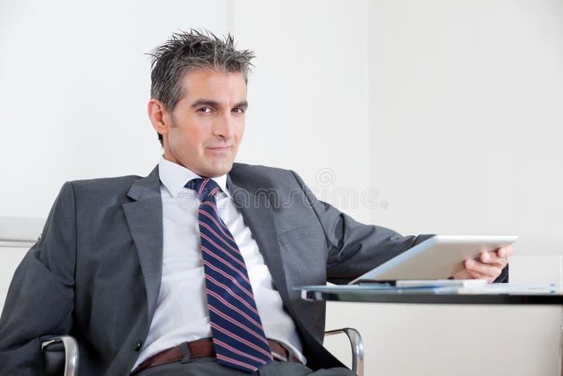 Homem de negócios Using Digital Tablet no escritório fotos de stock royalty free