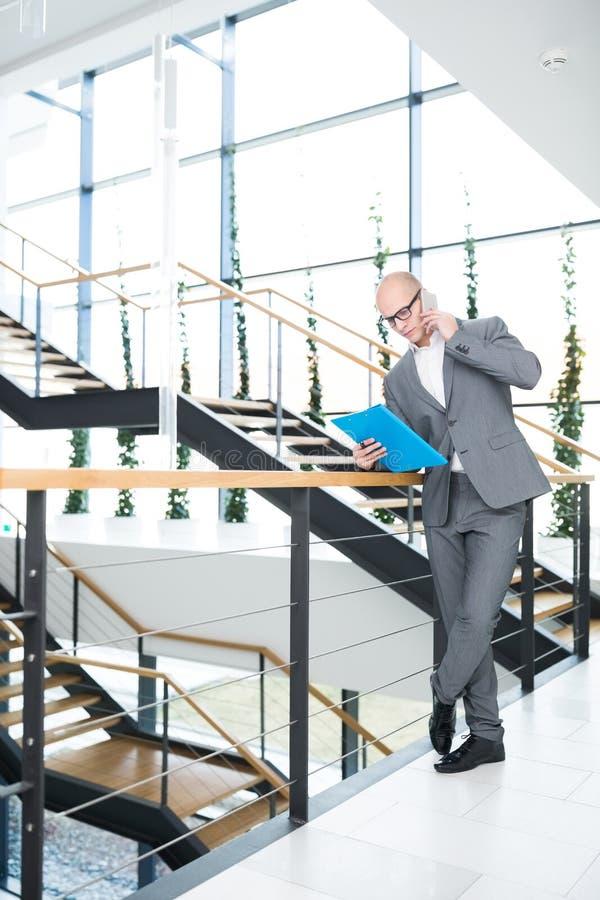 Homem de negócios Using Mobile Phone ao inclinar-se em trilhos foto de stock royalty free