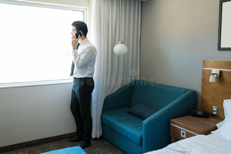 Homem de negócios Using Phone While que olha através da janela imagens de stock royalty free