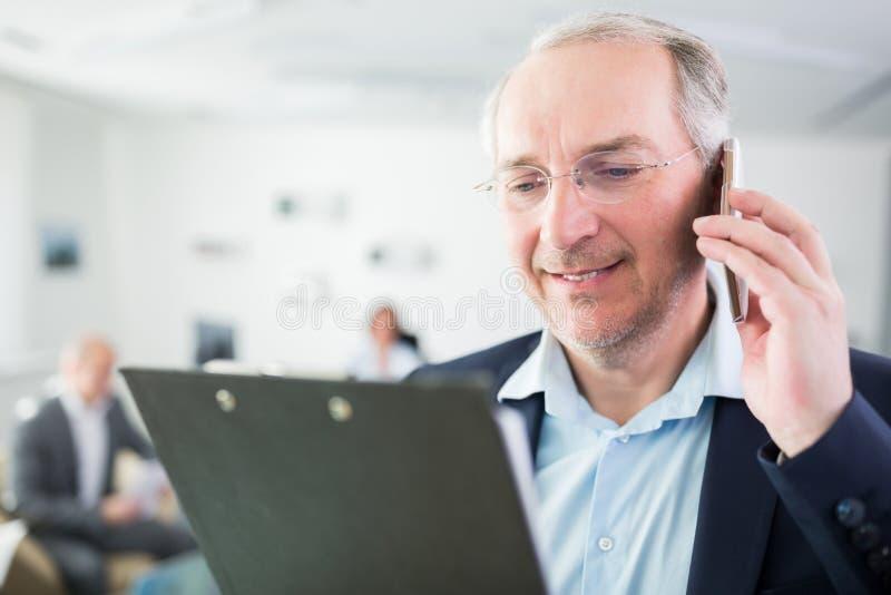 Homem de negócios Using Smartphone While que olha a prancheta imagens de stock royalty free