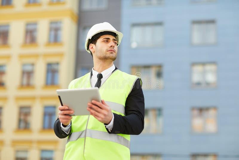 Homem de negócios Using Tablet no canteiro de obras imagens de stock royalty free