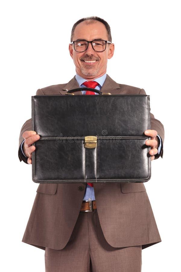 Homem de negócios velho feliz que mostra sua pasta foto de stock royalty free