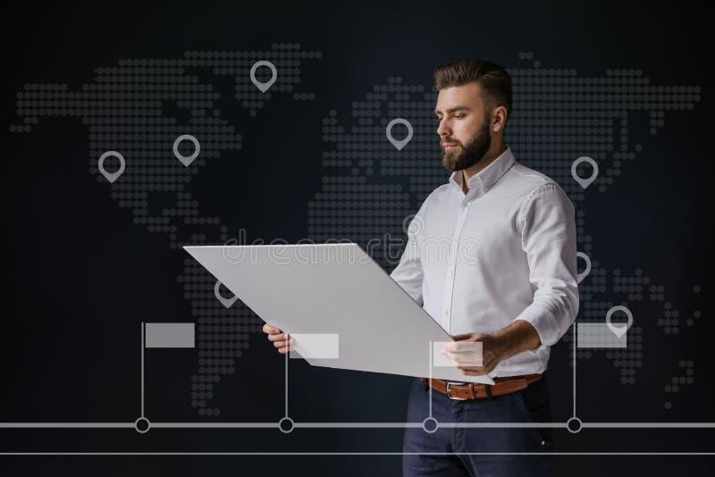 Homem de negócios, vestido na posição branca da camisa e guardando a tabuleta No mapa do mundo virtual do fundo com ícones dos po fotos de stock