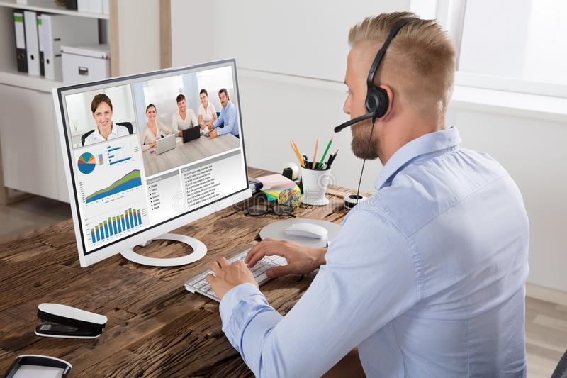 Homem de negócios Video Conferencing With Team On Computer fotografia de stock royalty free