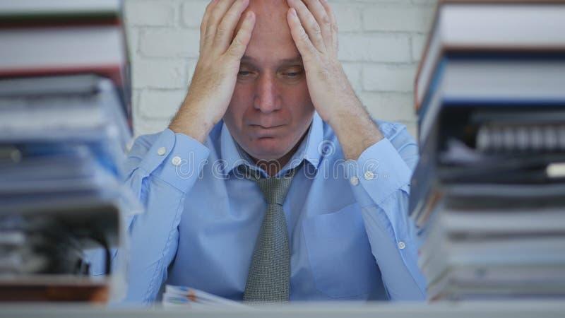 Homem de negócios virado e desapontado Image Sitting e pensamento no escritório fotos de stock royalty free