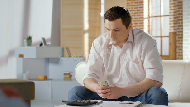 Homem de negócios virado no problema que conta o dinheiro, débito no empréstimo hipotecário, falência fotos de stock
