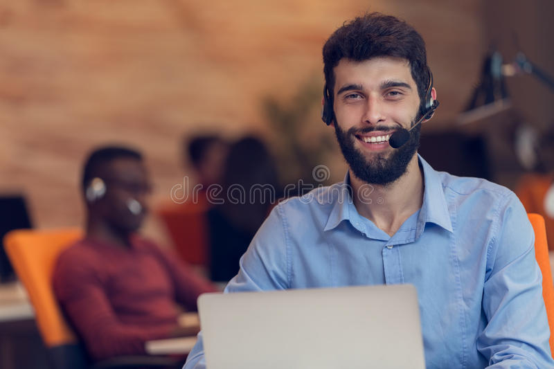 Homem de negócios Wearing Headphones Working no portátil no escritório fotos de stock