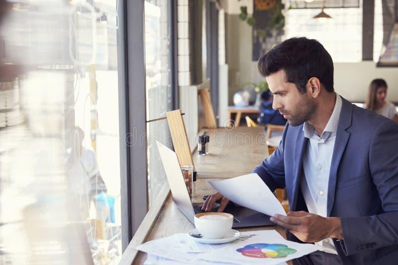 Homem de negócios By Window Working no portátil na cafetaria fotos de stock royalty free