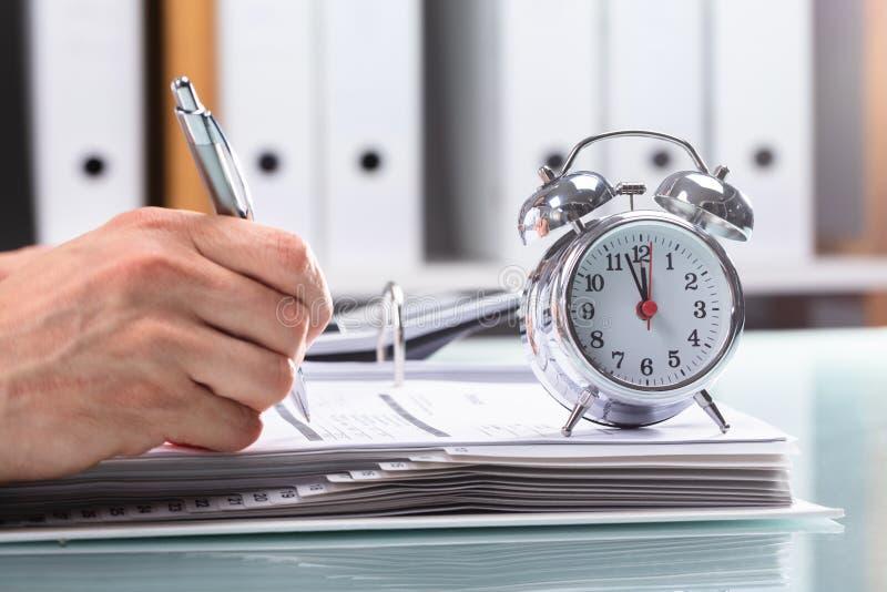 Homem de negócios Working On Document com alarme sobre a mesa imagem de stock royalty free