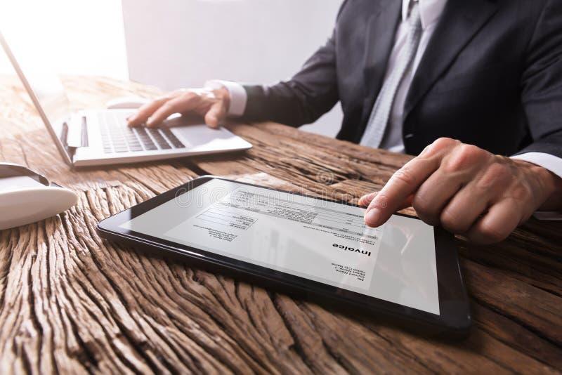 Homem de negócios Working With Invoice na tabuleta de Digitas imagens de stock royalty free