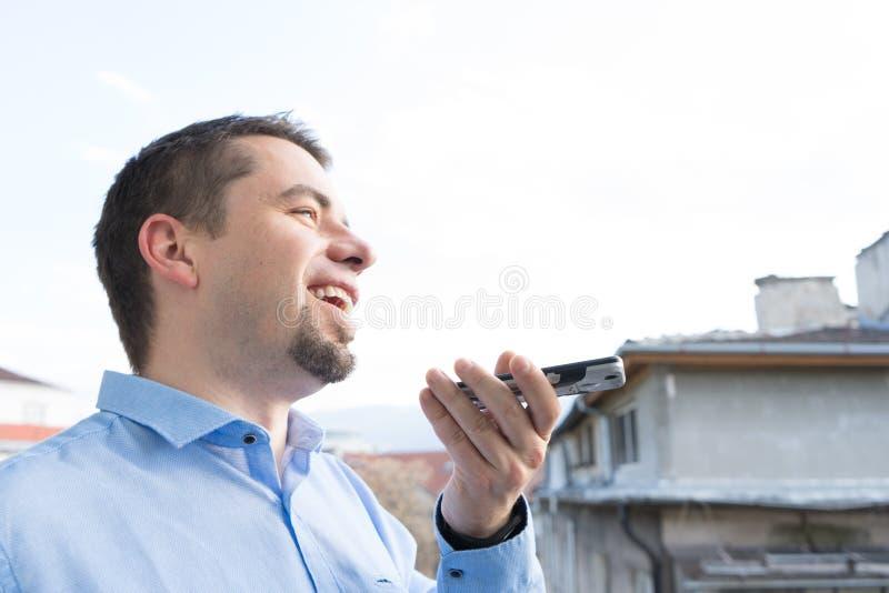 Homem de neg?cio novo feliz que envia a mensagem da voz por seu smartphone imagem de stock