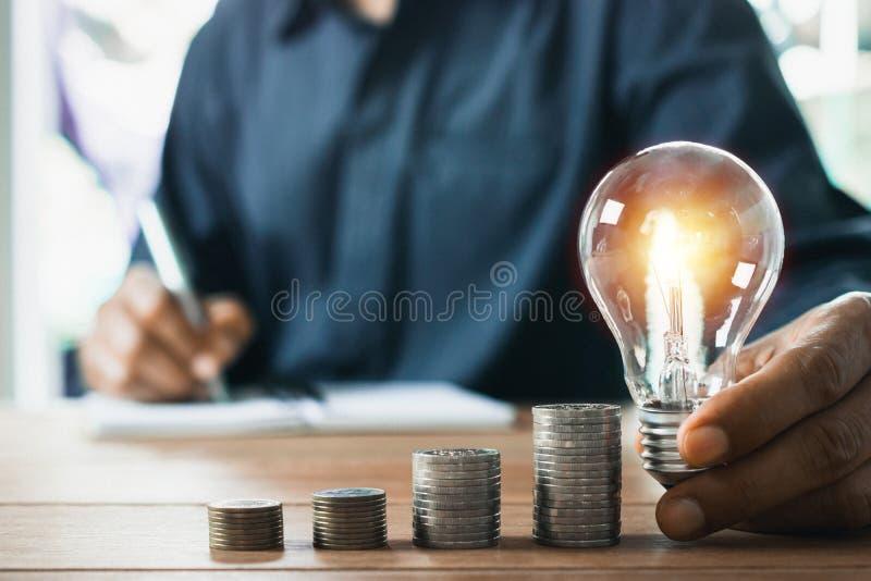 Homem de neg?cio que guarda a ampola na mesa no escrit?rio e que escreve no livro de nota a para financeiro, explicando, energia, imagem de stock