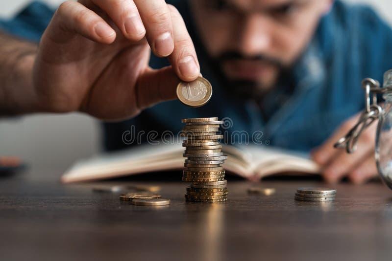 Homem de neg?cio que p?e uma moeda sobre o banco de economia da pilha das moedas e para esclarecer seu dinheiro todo no conceito  fotos de stock