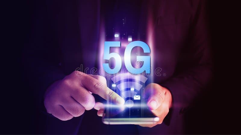 Homem de neg?cio que usa o smartphone m?vel com fluxo dos ?cones 5G no conceito da tela virtual imagens de stock