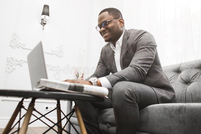 Homem de neg?cios afro-americano novo em um terno cinzento que trabalha atr?s de um port?til fotografia de stock
