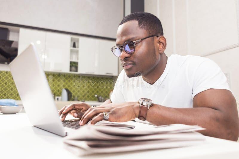 Homem de neg?cios afro-americano novo que trabalha em um port?til na cozinha em um interior moderno imagem de stock