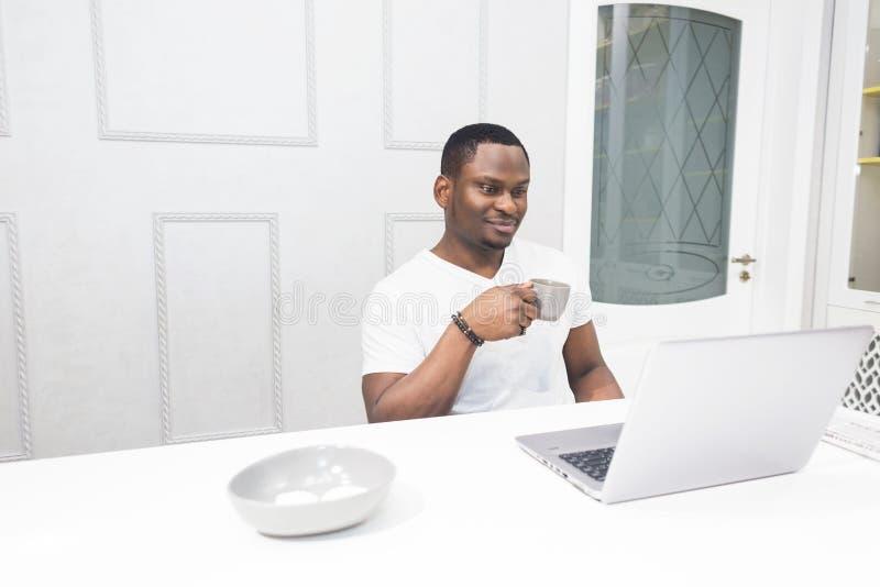 Homem de neg?cios afro-americano novo que trabalha em um port?til na cozinha em um interior moderno foto de stock