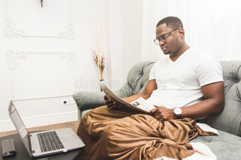 Homem de neg?cios afro-americano novo que trabalha remotamente em casa em um port?til fotos de stock royalty free