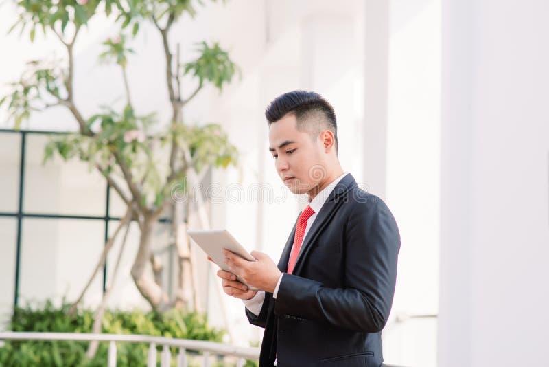 Homem de neg?cios asi?tico novo que trabalha na tabuleta, estilo de vida do homem moderno tecnologia para comunicar-se, de mensag fotos de stock royalty free