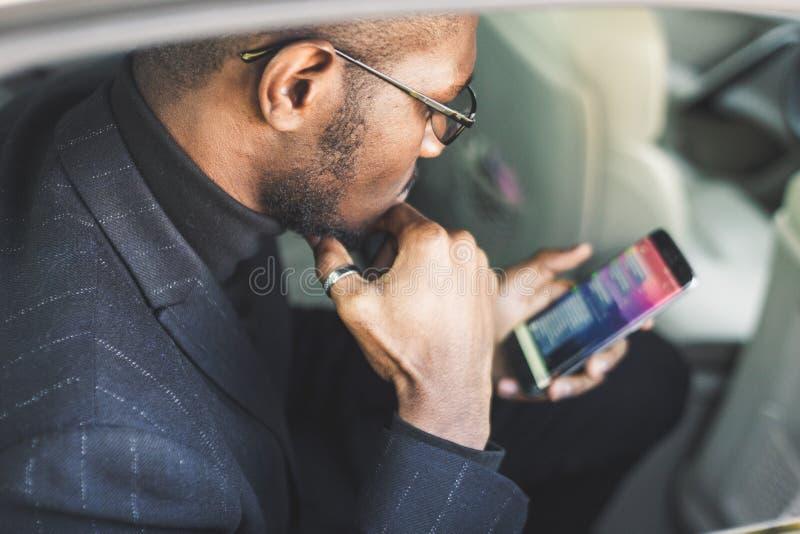 Homem de neg?cios bem sucedido novo que fala no telefone que senta-se no assento traseiro de um carro caro Negocia??es e neg?cio fotos de stock royalty free
