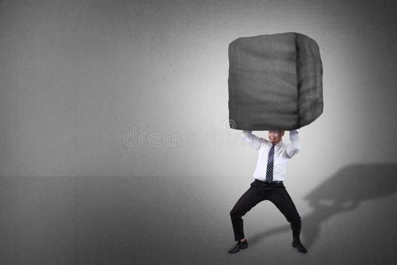 Homem de neg?cios Carrying Heavy Stone fotografia de stock