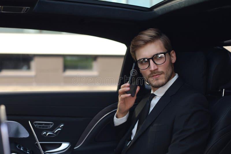 Homem de neg?cios consider?vel que fala com o telefone que senta-se com o port?til no assento traseiro do carro foto de stock royalty free