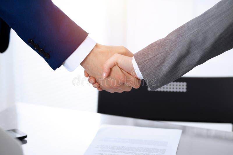 Homem de neg?cios e mulher de neg?cio que agita as m?os entre si acima do contrato assinado Sucesso na negocia??o e no acordo imagem de stock