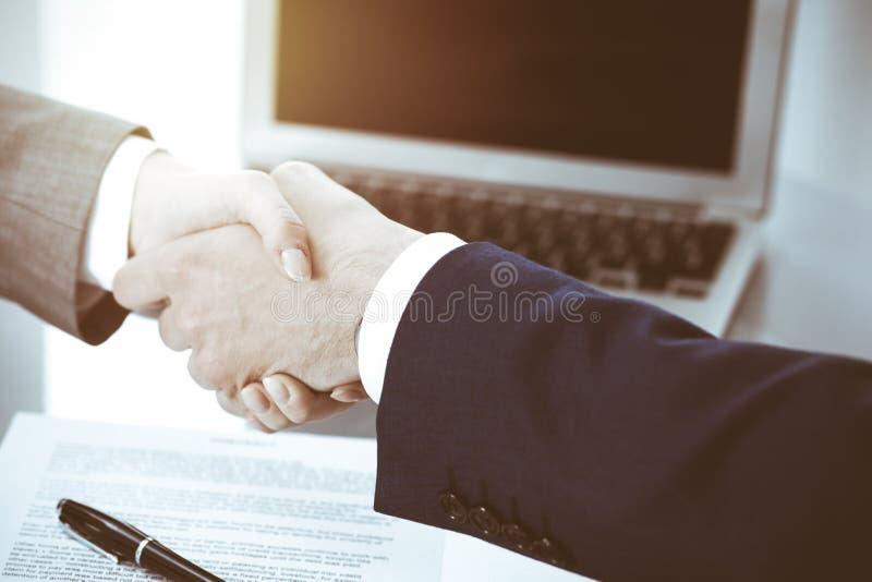 Homem de neg?cios e mulher de neg?cio que agita as m?os entre si acima do contrato assinado Sucesso na negocia??o e no acordo fotografia de stock