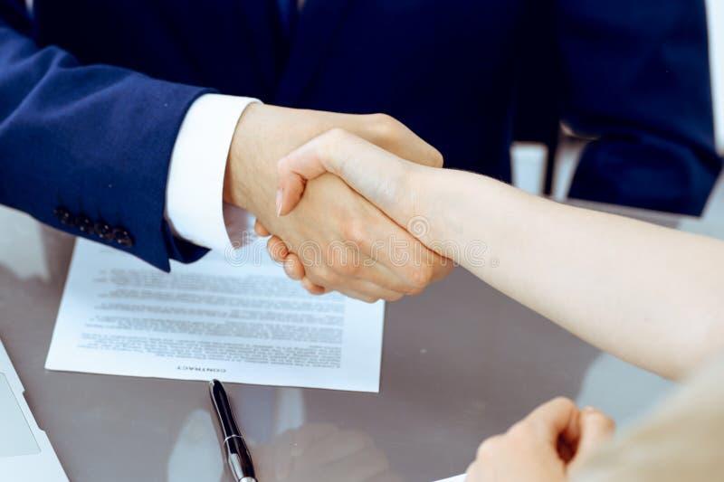 Homem de neg?cios e mulher de neg?cio que agita as m?os entre si acima do contrato assinado Sucesso na negocia??o e no acordo imagens de stock royalty free