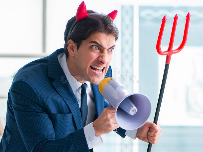 Homem de neg?cios irritado do diabo no escrit?rio imagem de stock
