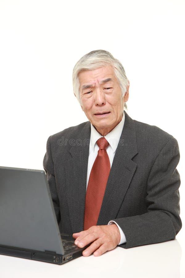 Homem de neg?cios japon?s superior que usa o computador que olha confundido foto de stock