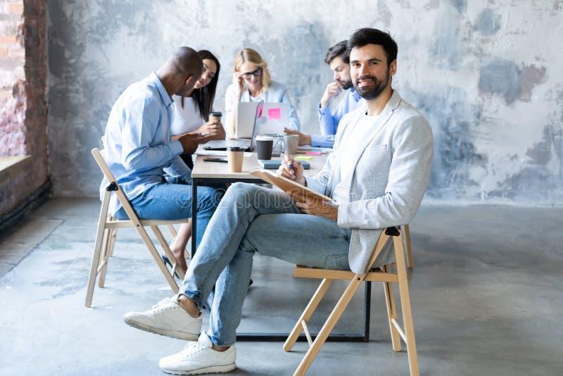 Homem de neg?cios moderno com um port?til que senta-se em uma cadeira confort?vel ? moda foto de stock royalty free