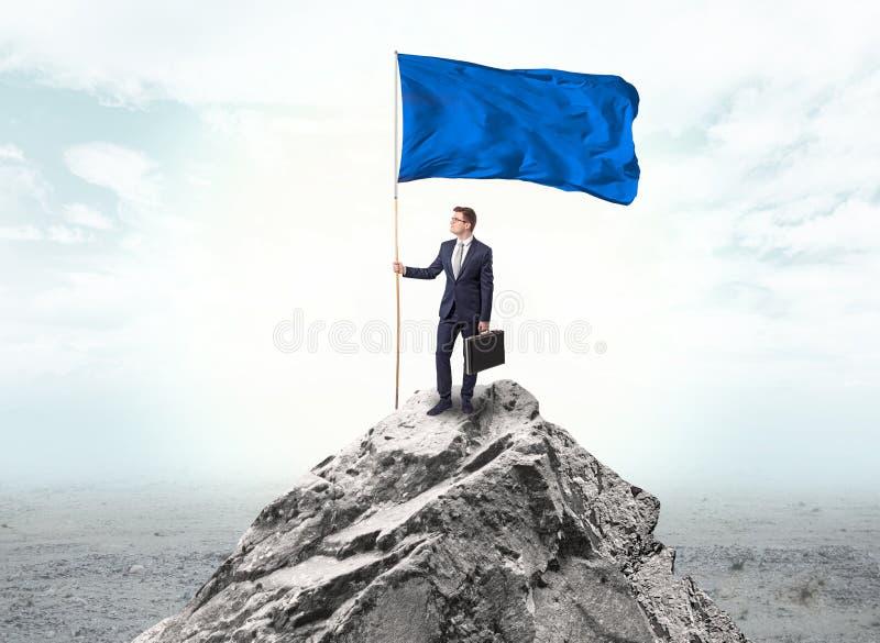 Homem de neg?cios na parte superior da montanha que guarda a bandeira imagens de stock