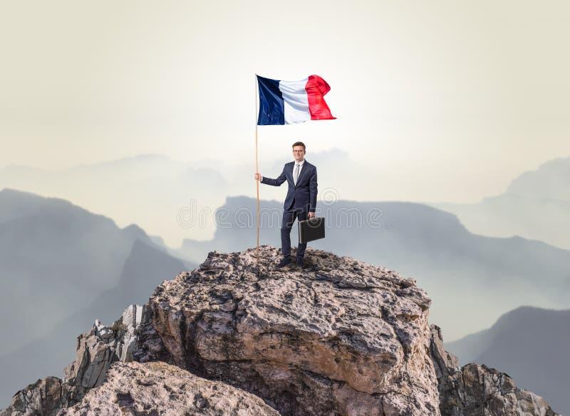 Homem de neg?cios na parte superior de uma rocha que guarda a bandeira fotografia de stock royalty free
