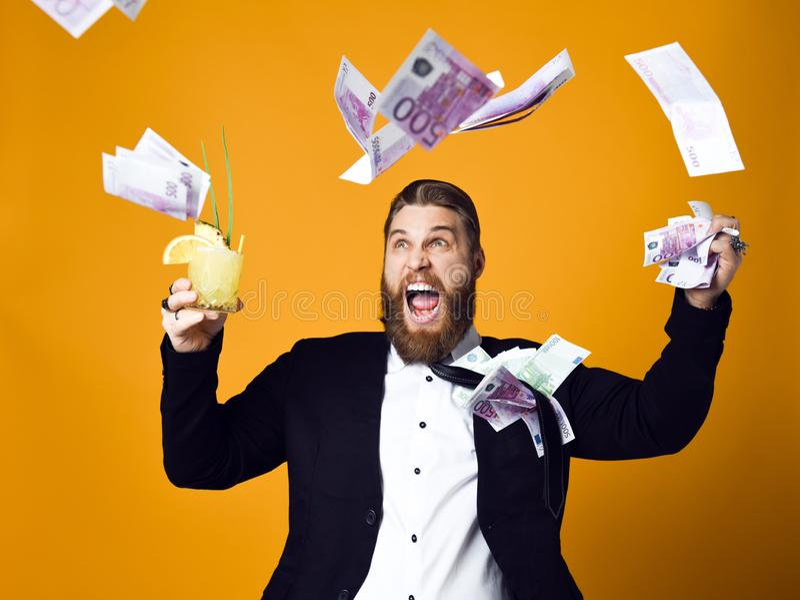Homem de neg?cios novo feliz com vidro do cocktail na roupa formal que guarda o grupo de c?dulas do dinheiro imagem de stock royalty free