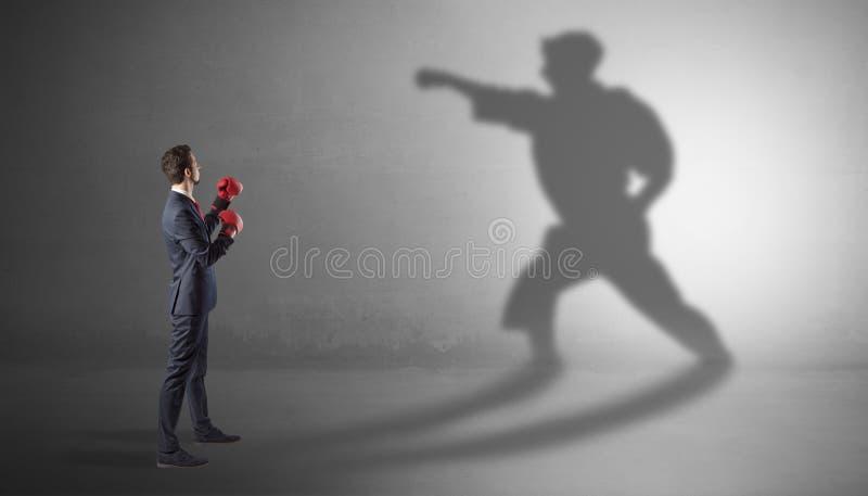 Homem de neg?cios novo que luta com sua sombra imagens de stock