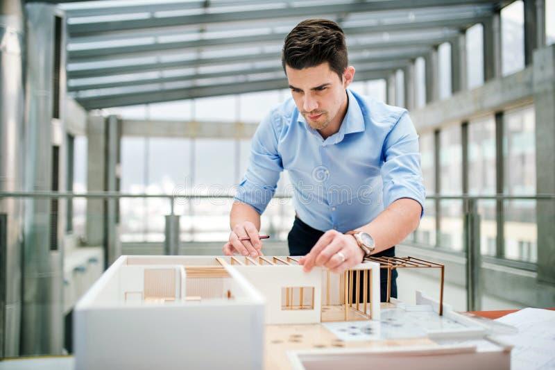 Homem de neg?cios ou arquiteto novo com o modelo de uma posi??o da casa no escrit?rio, trabalhando fotografia de stock royalty free