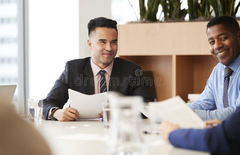 Homem de neg?cios With Paperwork Sitting na reuni?o da tabela com os colegas no escrit?rio moderno imagem de stock royalty free