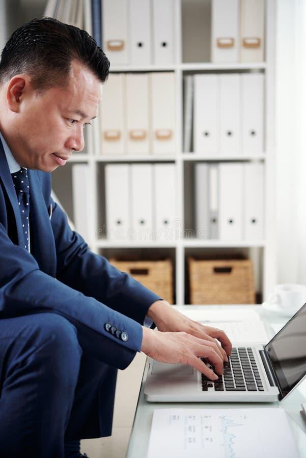 Homem de neg?cios que datilografa no computador port?til fotografia de stock royalty free