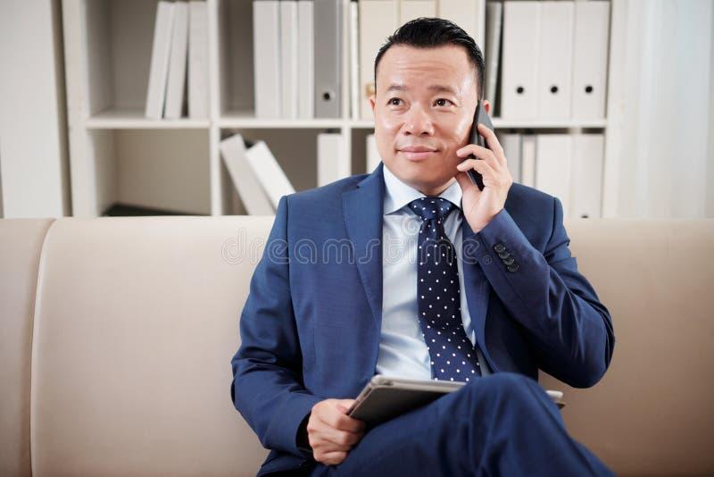 Homem de neg?cios que fala no telefone celular no escrit?rio imagem de stock royalty free