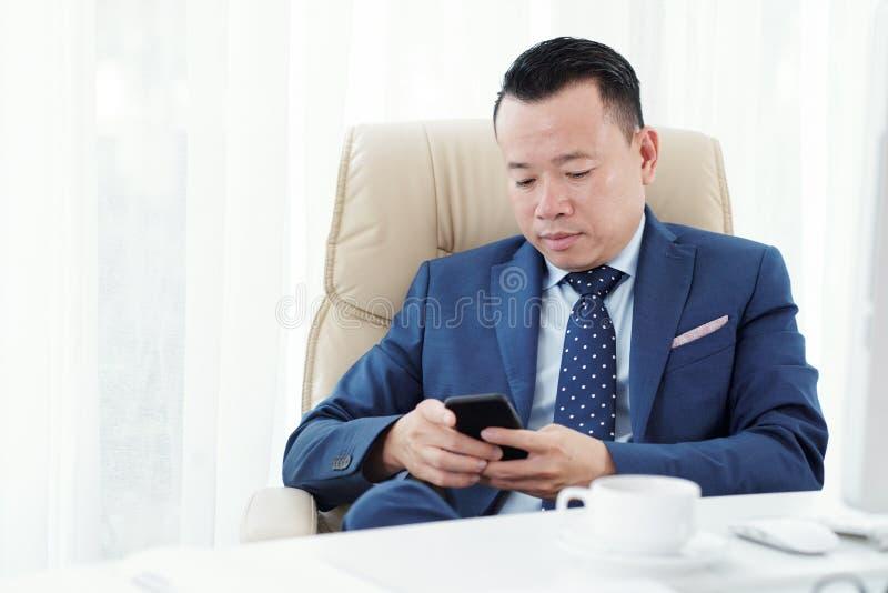 Homem de neg?cios que usa o telefone celular no escrit?rio imagem de stock royalty free