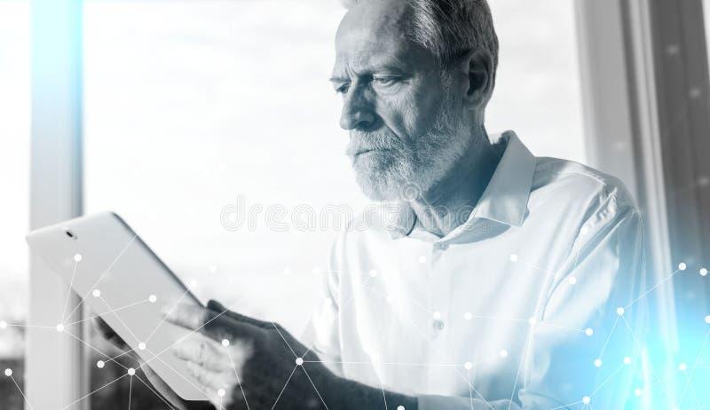 Homem de neg?cios superior que usa uma tabuleta digital, luz dura fotos de stock