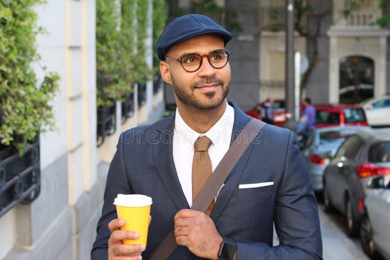 Homem de neg?cios ?tnico consider?vel que guarda o copo de caf? fora foto de stock royalty free