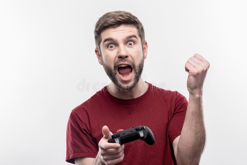 Homem de olhos azuis emocional que sente feliz ao jogar jogos de vídeo imagem de stock royalty free