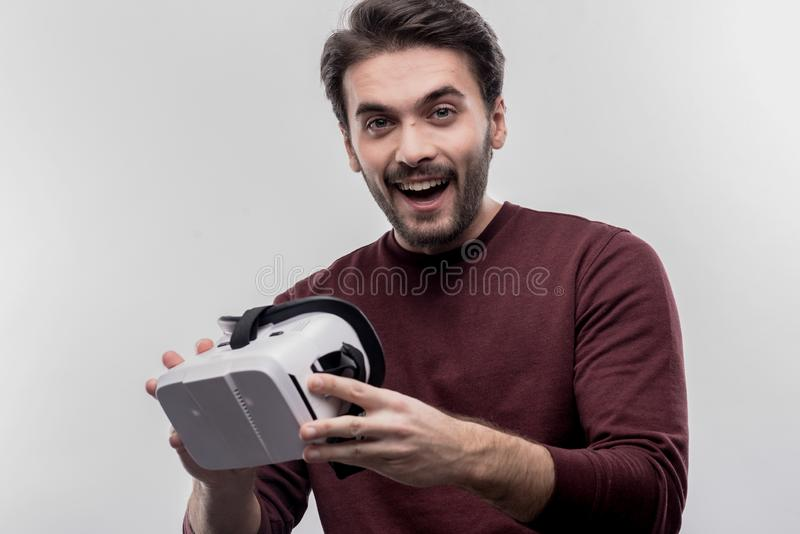 Homem de olhos verdes farpado considerável que guarda presente surpreendente nas mãos fotografia de stock