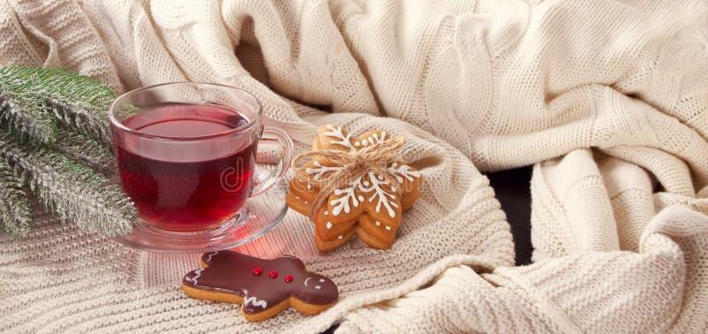 Homem de pão-de-espécie das cookies do Natal e flocos de neve engraçados, copo do chá na manta feita malha branca fotografia de stock royalty free