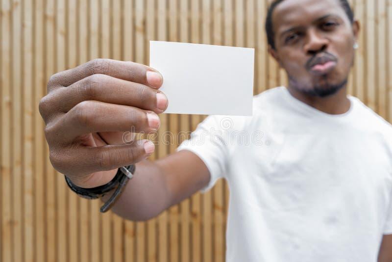 Homem de pele escura no t-shirt branco que mostra o cartão vazio à câmera foto de stock